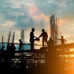 Imagem contra luz que mostra silhuetas de trabalhadores da construção civil durante uma obra