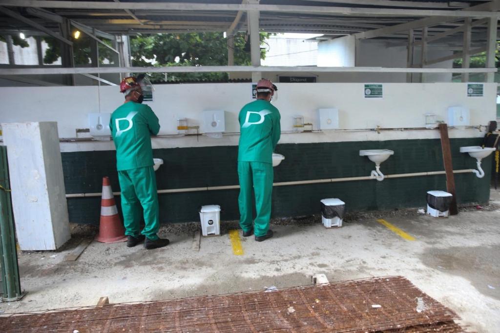 Foto mostra dois trabalhadores da construção civil higienizando as mãos em pias instaladas em canteiro de obra.